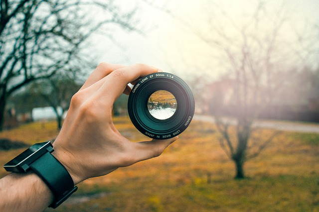 hand holding camera lens with aperture fully opened